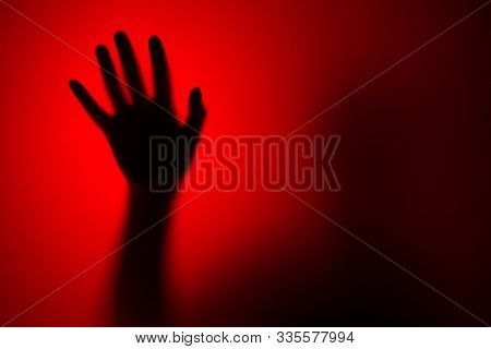 Silhouette of a female hand through glass on a red background. Horror concept