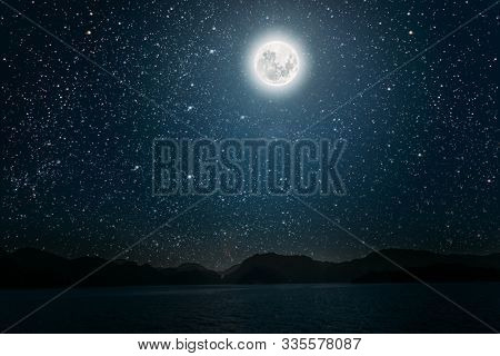 moon against a bright night starry sky reflected in the sea. Elements of this image furnished by NASA