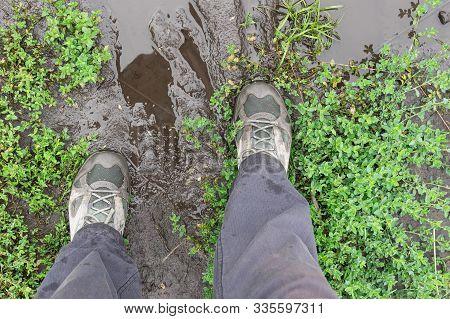 Top View On Men Feet Wearing Sneakers Standing On Miry Earth Road