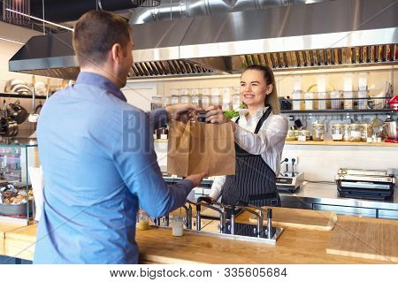Happy Waitress Waring Apron Serving Customer At Counter In Small Family Eatery Restaurant. Small Bus