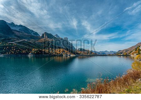 Overlooking The Fedaia Lake At The Foot Of The Marmolada Mountains In South Tyrol On A Sunny And Cle