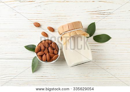 Glass Of Almond Milk And Almond Seeds On White Background, Space For Text. Top View