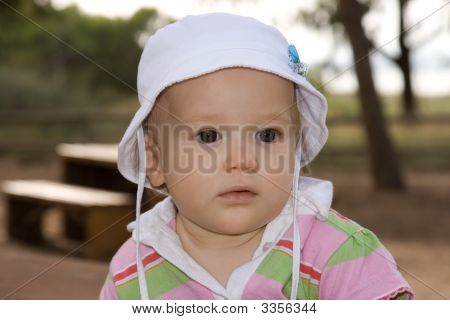 Beautiful And Happy Baby Girl With A White Cap
