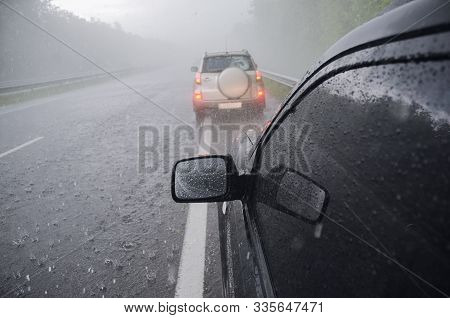 Two Cars In Heavy Stormy Rain And Hail
