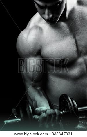 Muscular male bodybuilder doing biceps curl with dumbbell over dark background