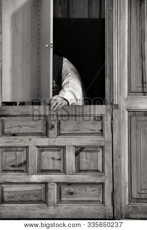 Priest In Confessional Confessing To A Faithful In Spain