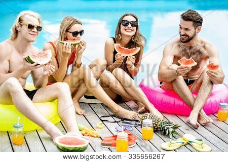 Group Of A Happy Friends In Swimwear Eating Watermelon While Sitting Together And Having Fun During