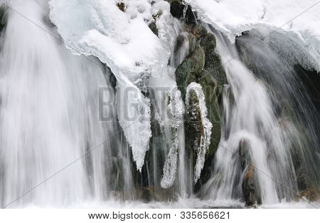 Beautiful Snowy Waterfall Flowing In The Mountains