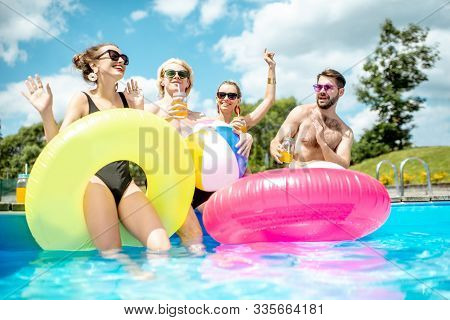 Group Of A Happy Friends Having Fun, Playing With Inflatable Balls And Rings On The Water Pool Outdo