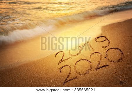 Goodbye 2019 Happy New Year 2020 Lettering On Sunset Beach With Wave And Sea. Handwritten Inscriptio
