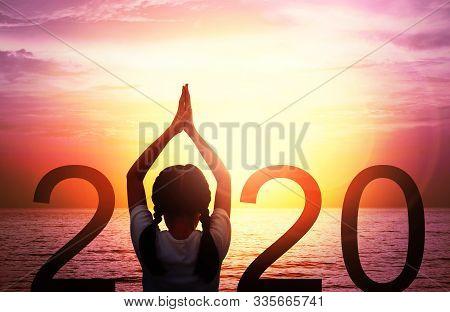 Happy New Year Card 2020. Silhouette Of Girl Doing Yoga Vrikshasana Tree Pose On Tropical Sea With F