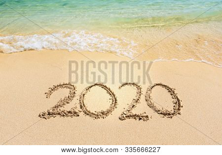 Happy New Year 2020, Lettering On The Beach With Wave And Clear Blue Sea. Numbers 2020 Year On The S