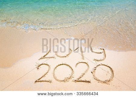 Goodbye 2019 Happy New Year 2020 Lettering On Beach With Wave And Clear Blue Sea On Sunny Day. Handw