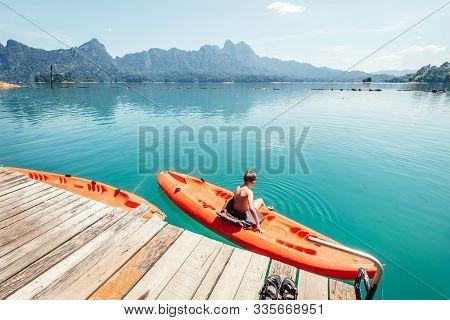 Little Boy Sitting On Orange Kayak Near The Pier And Dangling Feet Making Radial Waves On Cheow Lan