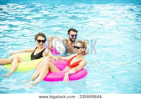 Group Of A Happy Friends Having Fun, Swimming With Inflatable Toys In The Swimming Pool Outdoors Dur