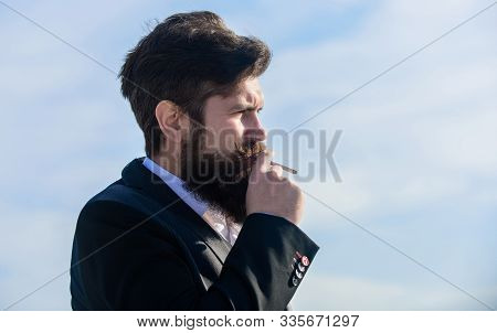 Bearded Hipster Smoking Cigarette Blue Sky Background. Guy With Cigarette Enjoy Nicotine Influence.