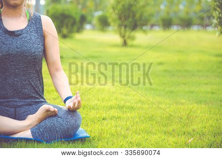 Woman Doing Yoga Outdoor. Woman Exercising Vital And Meditation For Fitness Lifestyle Club At The Ou