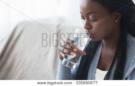 Thirsty African American Woman Drinking Clean Water From Glass At Home, Closeup