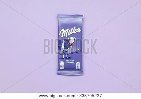 Milka Chocolate Tablet In Classic Violet Wrapping On Lilac Background. Milka Is Brand Of Chocolate C