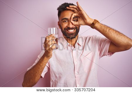 Young handsome indian man dinking glass of water over isolated pink background with happy face smiling doing ok sign with hand on eye looking through fingers