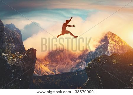 Man jumping between mountains at sunset. Concept of challenge, ambition, success. 3D illustration