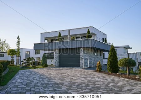 New Modern Cube-shaped House With A Garage In Front Of A Facade In A New Area Against A Blue Sky. Mo