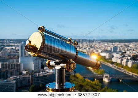 Binocular With Sunflare On Eiffel Tower Observation Deck With Paris Sunny Cityscape Background