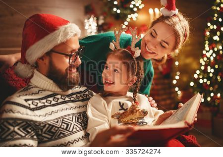 Christmas Eve. Family Father, Mother  And Child Reading Magic Book At Home Near The Fireplace And Th