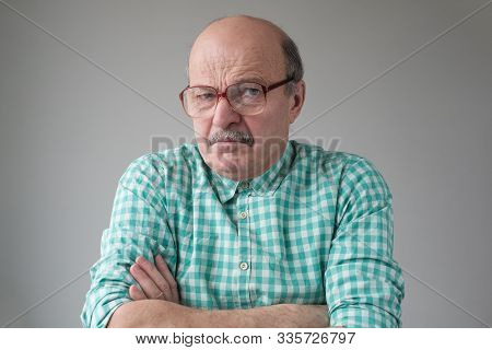 Angry Senior Man In Glasses Crossing Arms Looking Annoyed At Camera.