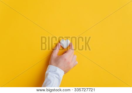 Male Hand Placing A Marble Heart Over Yellow Background. With Plenty Of Copy Space.