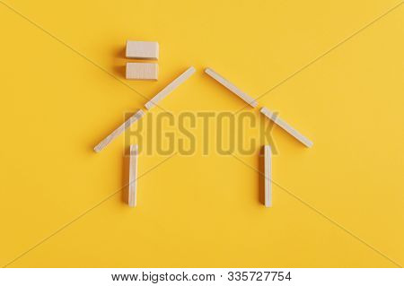 Shape Of A House Made Of Wooden Pegs And Blocks Over Yellow Background. With Copy Space.