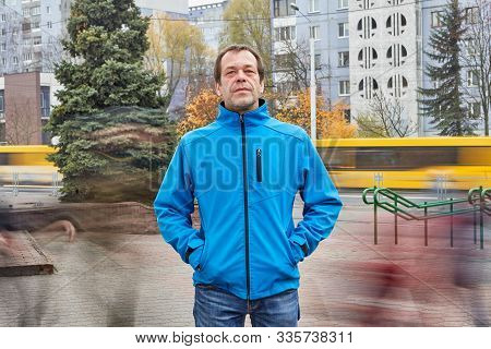 Mature Caucasian White Man About 50 Years Old In Blue Warm Jacket  Is Standing On The Street With Mo