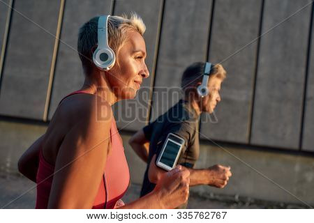 Morning Jog. Happy And Healthy Middle-aged Couple In Headphones Running Together Through The City St