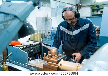 Worker Turner Operating Lathe Machine