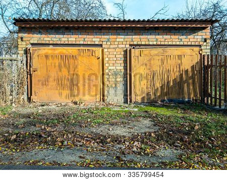 Old Detached Garage In Countryside. Garage Doors Covered By Plywood Damaged By Water And Humidity