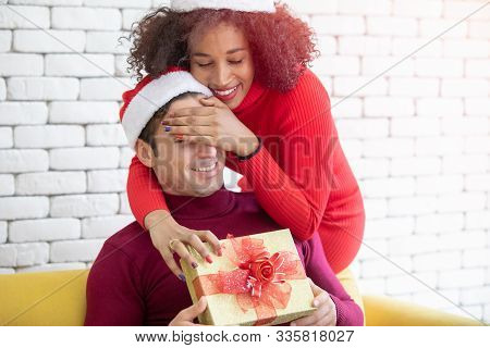 Young Caucasian Couple Celebrating Christmas Together. The Woman Close His Eyes And Gave Her Boyfrie