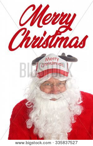 Santa Claus wears a Reindeer Antler Hat. Santa sits and models his Ball hat complete with antlers. Isolated on white with room for text. Merry Christmas.