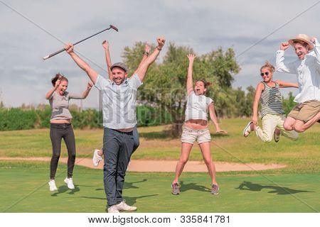 A Group Celebrating On A Golf Course