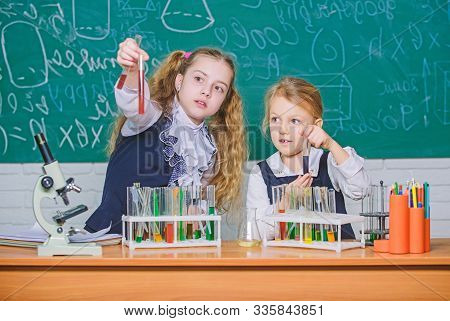 We Love Science. School Children Performing Experiment In Science Classroom. Little Girls Scientists