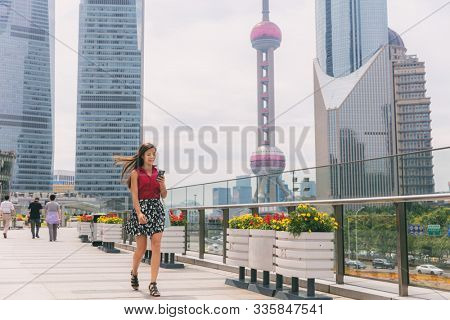 Business woman walking using phone commuting to work in Shanghai city, China. Tourist travel lifestyle Asian lady city street walk, cityscape in summer. View of Pearl Tower during morning commute.