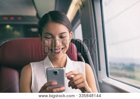Train travel mobile phone Asian business woman using cellphone texting during commute to work. Commuting people lifestyle on transport with 5g device.