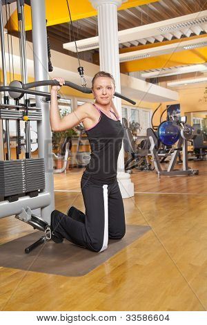 smiling young woman exercising in gym