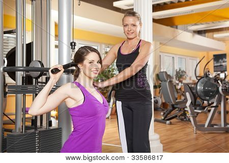 smiling young woman exercising in gym with trainer