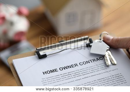 Close-up Of Realtors Hand Holding Homeowner Contract. Keys With Small Keychain. Wooden Home Model An