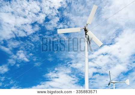 Wind Turbine At Wind Farm On Blue Sky. Alternative And Renewable Energy Concept. Sustainable Electri
