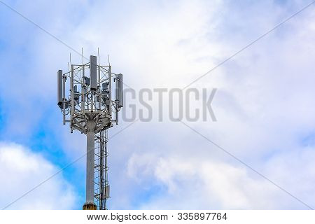 Cellular Communication Tower On A Background Of Cloudy Sky. Soft Focus. Concept: Communication And B