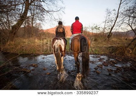 Two People On Horses Riding In The Nature