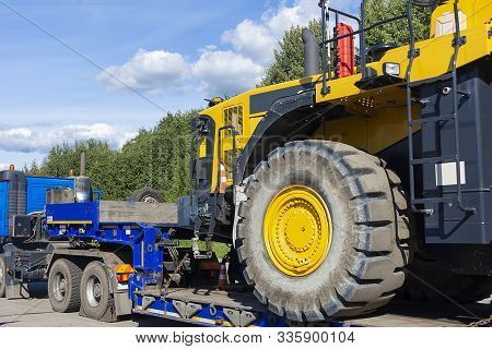 Large Truck With A Low Platform Trailer Carrying A Tractor. A Truck For Transporting Heavy Equipment