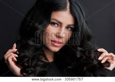 Studio portrait of seductive brunette woman touching curly hair by hand and posing on dark background. Elegant woman looking at camera. Hair Style and fashion concept.