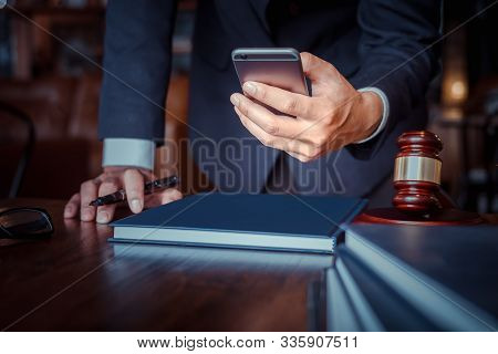 Justice And Law Concept. Gavel On Sounding Block In Hand's Male Judge At A Courtroom, Working With S